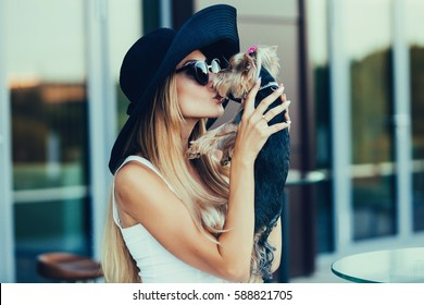 Beautiful young blond girl kissing small dog on journey