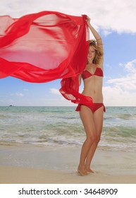 A beautiful young blond girl in a red bikini and a chiffon scarf stands in the tradewinds on Kailua beach, Oahu, Hawaii
