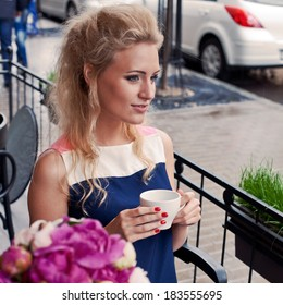 a beautiful young blond girl in summer dress at the table in pavement cafe holding a tea cup is looking thoughtfully in the distance