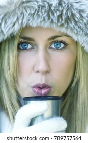 Beautiful young blond girl or young woman wrapped up warm in fur lined coat blowing onto a hot drink of coffee or tea