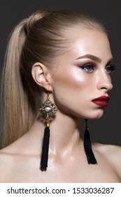Beautiful young blond model with professional makeup, long fashion earrings and ponytail hairstyle. Side view.