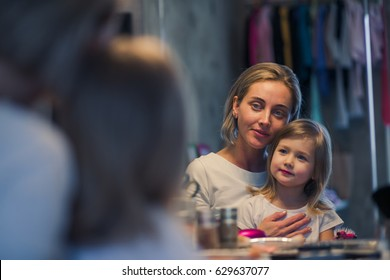 Beautiful young blond mother is hugging her cute little daughter in front of a dressing table.   Image with selective focus and toning