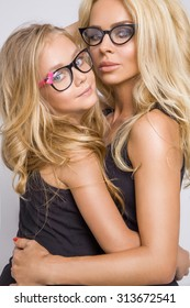 Beautiful young blond sexy mom of an adorable little baby girl with long hair in black glasses snuggling and looking the lens on a white background amazing green eyes blue