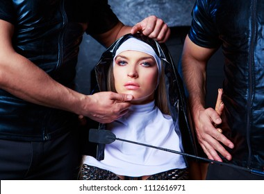 beautiful young blond striptease dancer dressed as a nun,with hands of two men,  in the interior