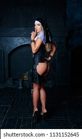 beautiful young blond striptease dancer dressed as a nun, in the interior