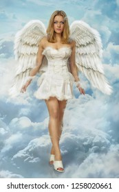 Beautiful young blond woman angel walking in the clouds heaven with white wings