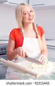 beautiful young blond woman baking in the kitchen at home