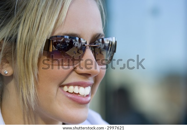 A beautiful young blond woman bathed in summer sunshine with a big smile and wearing sunglasses which reflect the cafe in which she is seated.
