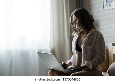 beautiful young blond woman in the bedroom on the bed in lingerie and shirt with a laptop