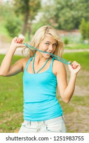 beautiful young blond woman in blue blouse with beads smiling at background of green summer park