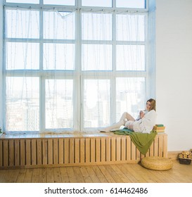 Beautiful young blond woman with cup of tea or coffee looking up on floor and sit near winter window on wooden windowsill at home. warm inside living room. big window frame