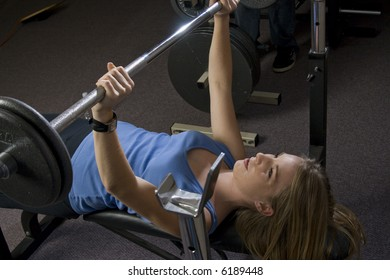 Beautiful young blond woman doing bench presses with weights in a fitness location.