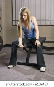 Beautiful young blond woman doing arm curls with a dumbbell in a fitness location.