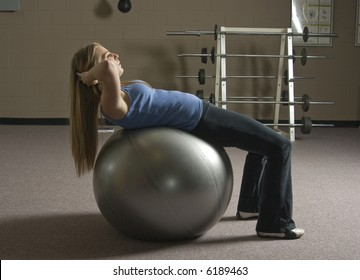 Beautiful young blond woman doing abdominal crunches on an exercise ball in a fitness location.