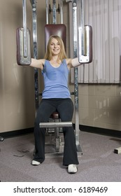 Beautiful young blond woman doing pectoral muscle exercise in a fitness location.