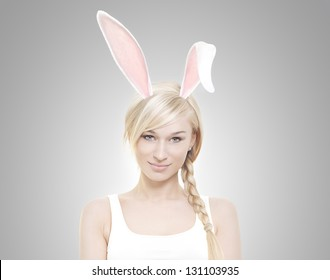 Beautiful young blond woman as easter bunny with rabbit ears on grey background