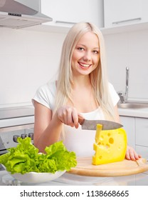 beautiful young blond woman eating cheese at home in the kitchen