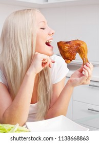 beautiful young blond woman eating fried chicken at home in the kitchen