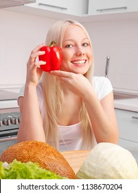 beautiful young blond woman eating at home in the kitchen
