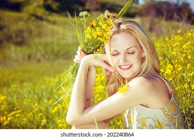 beautiful young blond woman with flowers smiling sitting down in the meadow of flowers, pretty girl relaxing outdoor, happy young lady and green spring nature in harmony