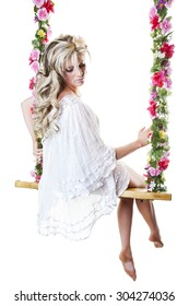 Beautiful young blond woman in a flowing white nightgown, perched on a dreamy floral covered swing.  Shot on white background.