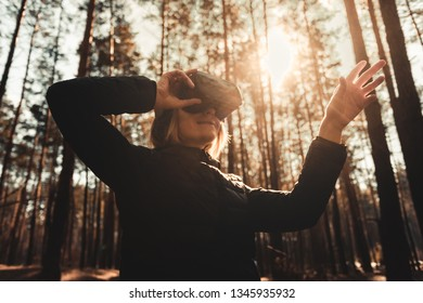 Beautiful young blond woman in forest with virtual reality headset looking straight and trying to touch something with her hand. vr glasses, technologies concept.