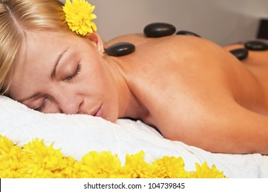 Beautiful young blond woman getting a stone massage in spa salon