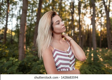 Beautiful young blond woman in a glamorous pink striped sundress relaxes standing in the forest on a sunny hot summer day. Attractive sexy photo model girl enjoys the sun outdoors. Fashion.