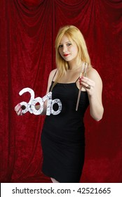 beautiful young blond woman with glass of champagne on red velvet background