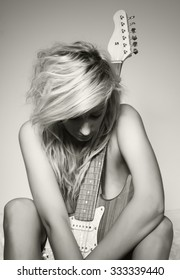 A beautiful young blond woman holding a guitar with her eyes closed. Sexy musician