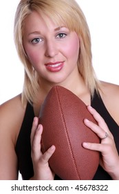 a beautiful young blond woman holding an american football.