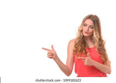 Beautiful young blond woman with long curly hair, in red dress, standing isolated on white background and pointing at copy space with two hands index fingers, with a smirk on her face