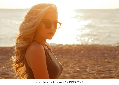 Beautiful young blond woman on the beach at sunset