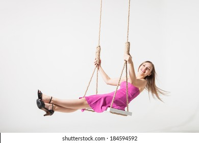 beautiful young blond woman on a swing against white studio background