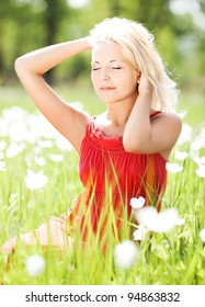 beautiful young blond woman  on the  meadow with white flowers  on a warm summer day