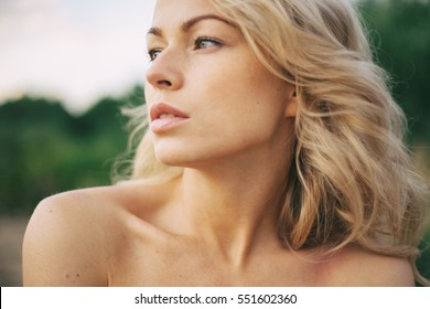 Beautiful young blond woman outdoors. Sunny day. Nature summer background. Outside close-up portrait of beautiful young happy woman with fresh and clean skin.