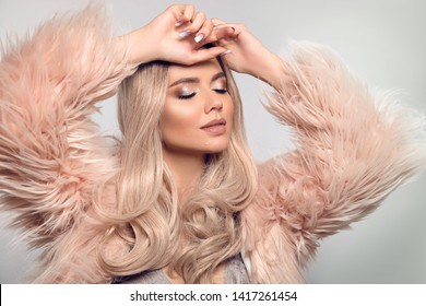 Beautiful young blond woman in pink fur coat. Winter fashion. Beauty Sexy Model Girl with long curly shiny hair and make-up isolated on grey studio background.