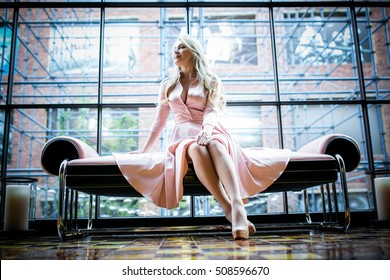 Beautiful young blond woman in pink dress sitting on the bench