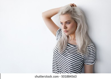 beautiful young blond woman posing while leaning on white wall with copy space. Hipster girl with blue eyes and bleached silver hair