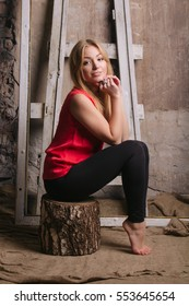 beautiful young blond woman in a red blouse posing on the background of a concrete wall in the studio.