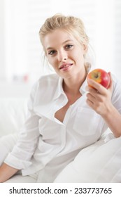 beautiful young blond woman resting on a white couch and eating an apple