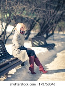 Beautiful young blond woman sitting on a bench in winter coat and red boots. Winter sunny evening.