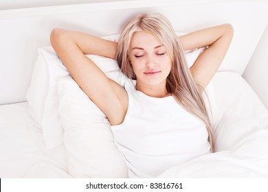 beautiful young blond woman sleeping in bed at home