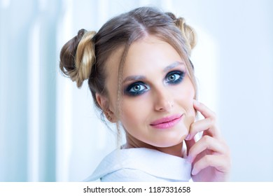 beautiful  young blond woman with sparkling silver makeup posing  in the  studio