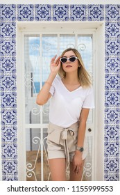 Beautiful young blond woman standing at the wall covered with portuguese traditional tiles azulejo.