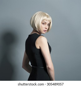 beautiful young blond woman in a strict black dress in the studio on the move with short hair stands sideways