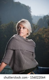 Beautiful young blond woman in a stylish cowl-neck sweater standing against a backdrop of misty forested mountain peaks looking thoughtfully up into the air