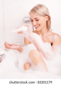 beautiful young blond woman taking a relaxing bath with foam and using cosmetics