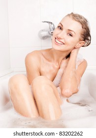 beautiful young blond woman taking a relaxing bath with foam and washing her hair