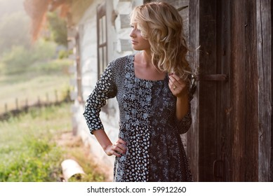 Beautiful young blond woman thoughtfully standing near old country house in the sunset light